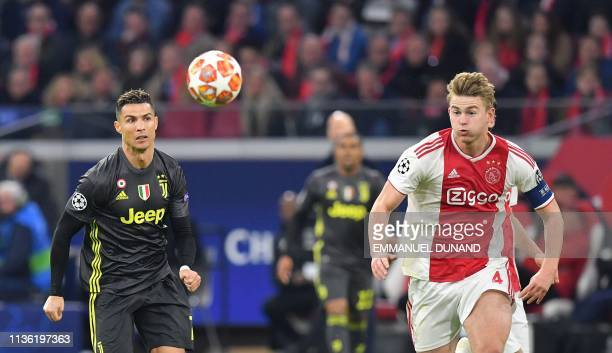 Juventus' Portuguese forward Cristiano Ronaldo and Ajax's Dutch defender Matthijs de Ligt run for the ball during the UEFA Champions League first leg...