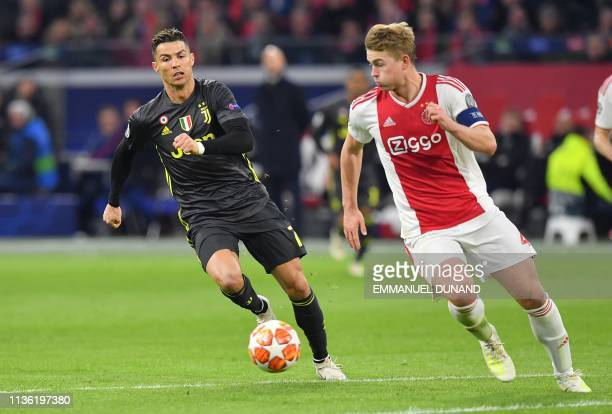 Juventus' Portuguese forward Cristiano Ronaldo and Ajax's Dutch defender Matthijs de Ligt run with the ball during the UEFA Champions League first...