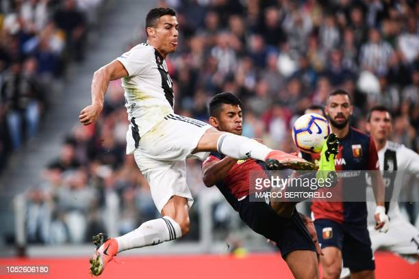 Juventus' Portuguese forward Cristiano Ronaldo and Genoa's Argentine defender Cristian Romero go for the ball during the Italian Serie A football...