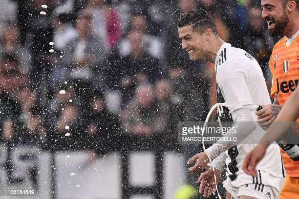 Juventus' Portuguese forward Cristiano Ronaldo and Juventus' Italian goalkeeper Carlo Pinsoglio celebrate with champagne after Juventus secured its...