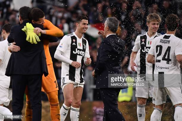Juventus' Portuguese forward Cristiano Ronaldo and teammates celebrate after Juventus secured its 8th consecutive Italian 2018/19 Scudetto Serie A...