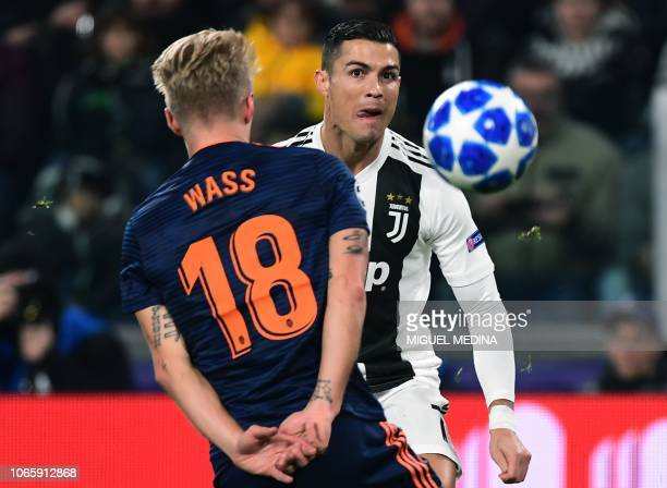 Juventus' Portuguese forward Cristiano Ronaldo and Valencia's Danish midfielder Daniel Wass go for the ball during the UEFA Champions League group H...