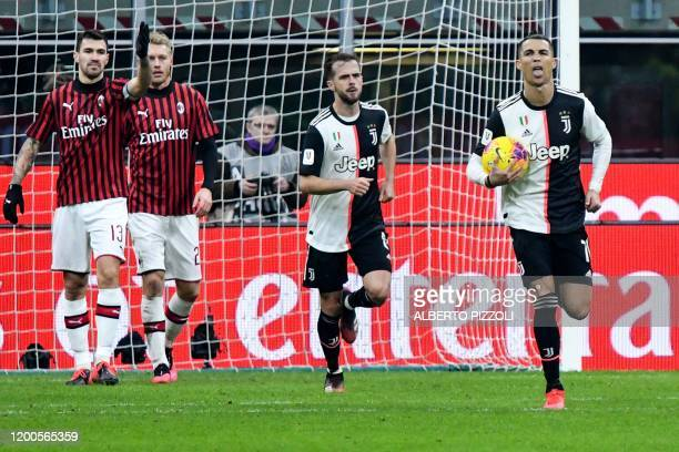 Juventus' Portuguese forward Cristiano Ronaldo celebrates after scoring a penalty as AC Milan's Italian defender Alessio Romagnoli reacts during the...