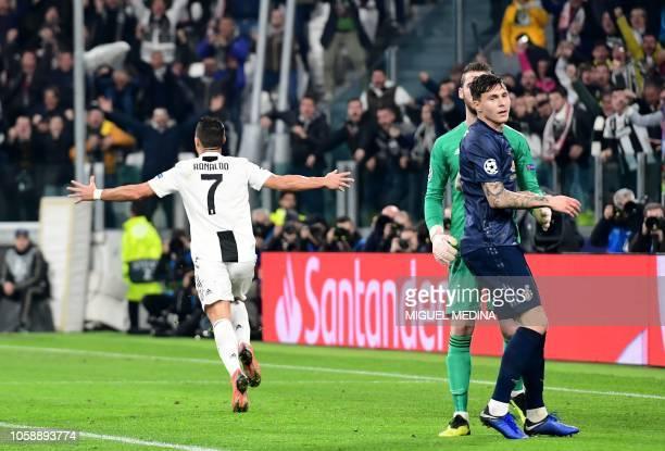 Juventus' Portuguese forward Cristiano Ronaldo celebrates after opening the scoring as Manchester United's Swedish defender Victor Lindelof looks on...