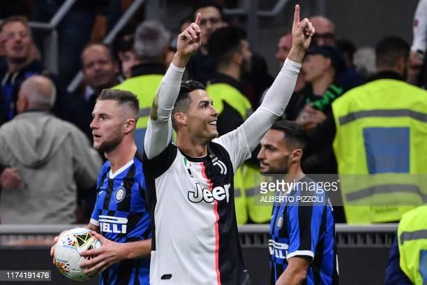 Juventus' Portuguese forward Cristiano Ronaldo celebrates as Inter Milan's Slovakian defender Milan Skriniar and Inter Milan's Italian defender...