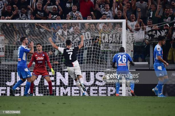 Juventus' Portuguese forward Cristiano Ronaldo celebrates as Napoli's Senegalese defender Kalidou Koulibaly scores an own goal during the Italian...