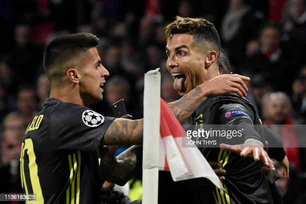 Juventus' Portuguese forward Cristiano Ronaldo celebrates with teammates after scoring a goal during the UEFA Champions League first leg quarterfinal...