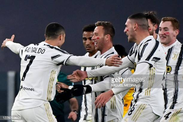 Juventus' Portuguese forward Cristiano Ronaldo celebrates with Juventus' Brazilian midfielder Arthur and teammates after opening the scoring during...