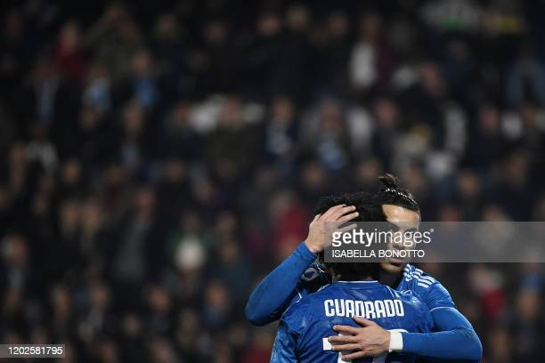 Juventus' Portuguese forward Cristiano Ronaldo celebrates with Juventus' Colombian midfielder Juan Cuadrado after opening the scoring during the...