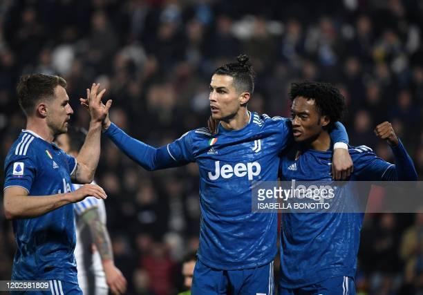Juventus' Portuguese forward Cristiano Ronaldo celebrates with Juventus' Colombian midfielder Juan Cuadrado and Juventus' Welsh midfielder Aaron...