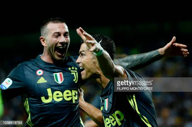 Juventus' Portuguese forward Cristiano Ronaldo celebrates with teammate Juventus's Italian forward Federico Bernardeschi during the Italian Serie A...