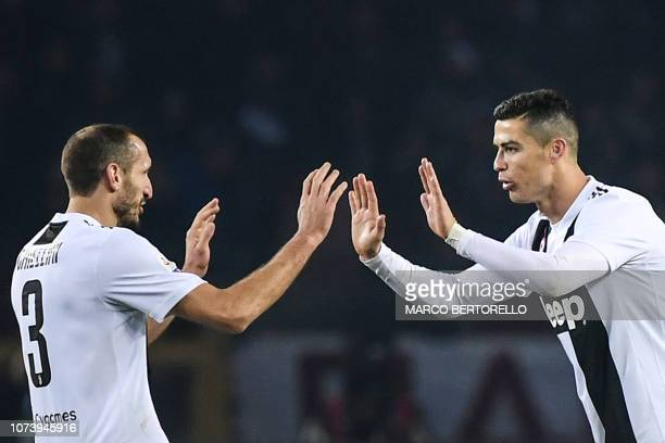 Juventus' Portuguese forward Cristiano Ronaldo celebrates with Juventus' Italian defender Giorgio Chiellini after opening the scoring with a penalty...