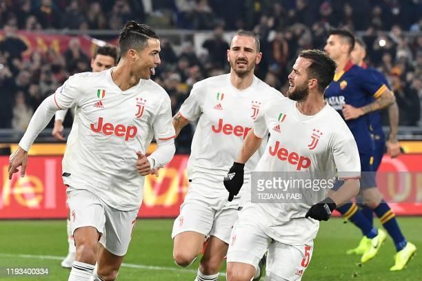 Juventus' Portuguese forward Cristiano Ronaldo celebrates with Juventus' Bosnian midfielder Miralem Pjanic and Juventus' Italian defender Leonardo...