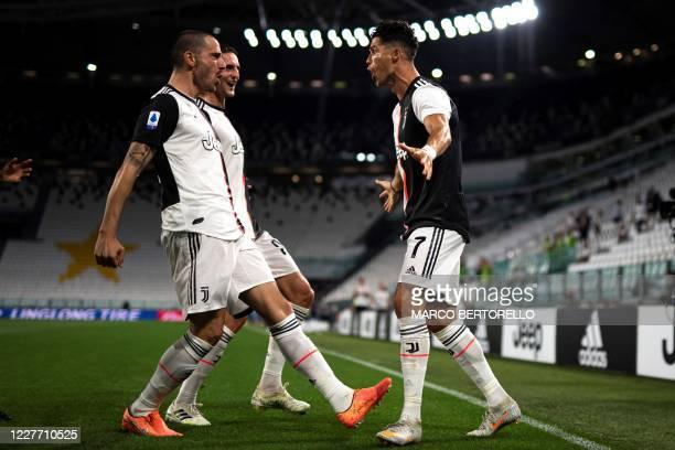 Juventus' Portuguese forward Cristiano Ronaldo celebrates with Juventus' Italian defender Leonardo Bonucci and Juventus' French midfielder Adrien...