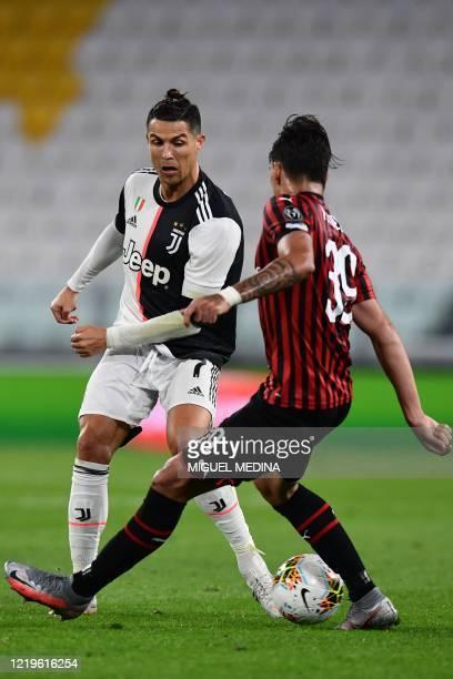 Juventus' Portuguese forward Cristiano Ronaldo challenges AC Milan's Brazilian midfielder Lucas Paqueta during the Italian Cup semi-final second leg...