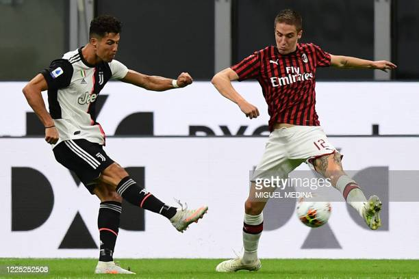 Juventus' Portuguese forward Cristiano Ronaldo challenges AC Milan's Italian defender Andrea Conti during the Italian Serie A football match AC Milan...