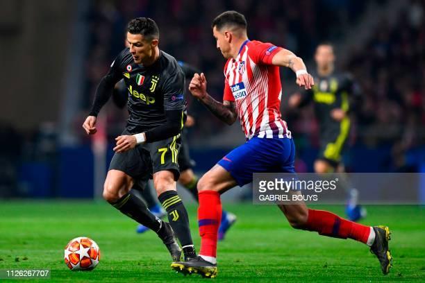 Juventus' Portuguese forward Cristiano Ronaldo challenges Atletico Madrid's Uruguayan defender Jose Gimenez during the UEFA Champions League round of...