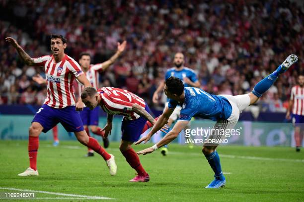 Juventus' Portuguese forward Cristiano Ronaldo challenges Atletico Madrid's Montenegrin defender Stefan Savic and Atletico Madrid's English defender...