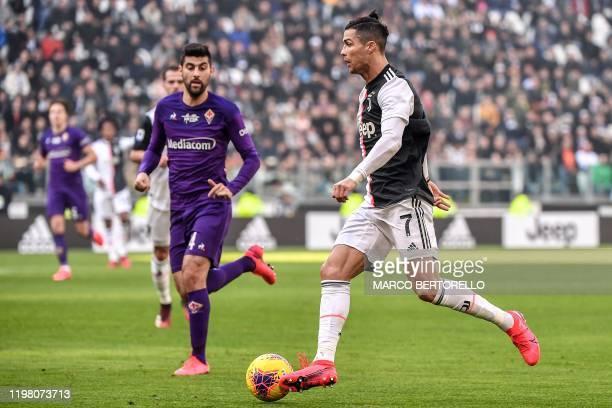 Juventus' Portuguese forward Cristiano Ronaldo challenges Fiorentina's Italian midfielder Marco Benassi during the Italian Serie A football match...