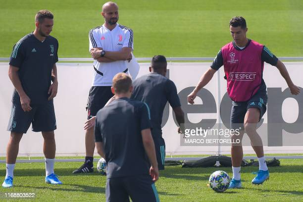 Juventus' Portuguese forward Cristiano Ronaldo challenges Juventus' Brazilian defender Alex Sandro during a training session on September 17 2019 at...