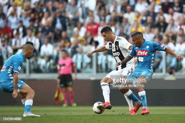 Juventus' Portuguese forward Cristiano Ronaldo challenges Napoli's Brazilian midfielder Allan and Napoli's Slovak midfielder Marek Hamsik during the...