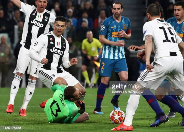 Juventus' Portuguese forward Cristiano Ronaldo collides with Atletico Madrid's Slovenian goalkeeper Jan Oblak during the UEFA Champions League round...