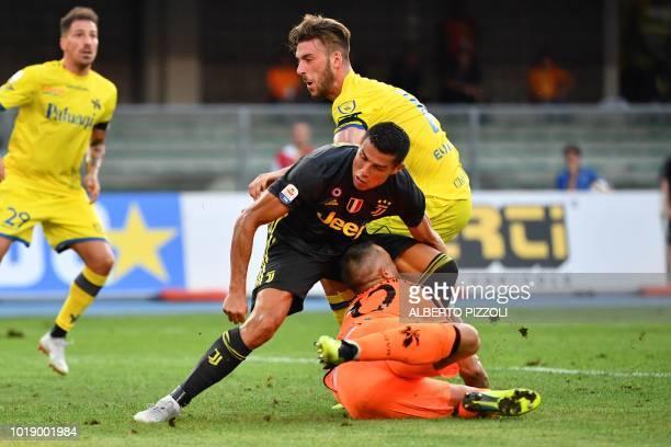 Juventus' Portuguese forward Cristiano Ronaldo collides with Chievo's goalkeeper Stefano Sorrentino during the Italian Serie A football match AC...