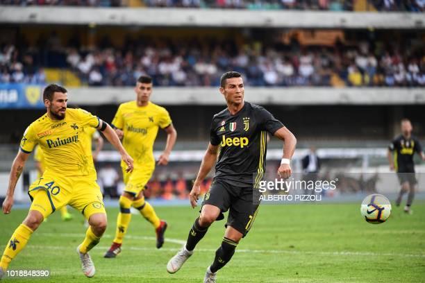 Juventus' Portuguese forward Cristiano Ronaldo controls the ball under pressure from Chievo's Serbian defender Nenad Tomovic during the Italian Serie...