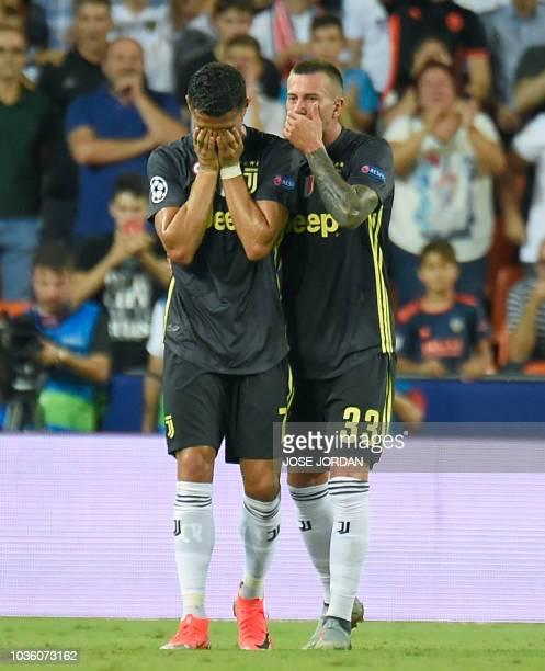 Juventus' Portuguese forward Cristiano Ronaldo cries next to Juventus' Italian midfielder Federico Bernardeschi after receiving a red card during the...