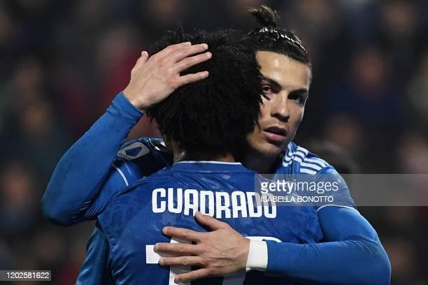 Juventus' Portuguese forward Cristiano Ronaldo embraces Juventus' Colombian midfielder Juan Cuadrado after opening the scoring during the Italian...