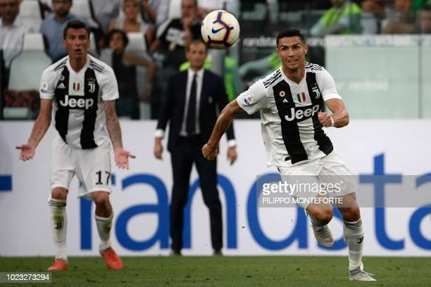 Juventus' Portuguese forward Cristiano Ronaldo eyes the ball as Juventus' Croatian forward Mario Mandzukic reacts during the Italian Serie A football...