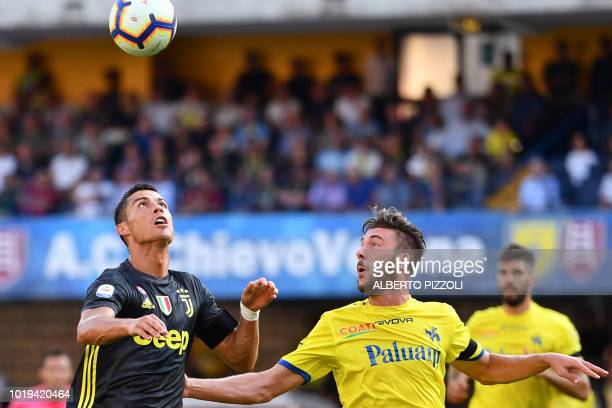 Juventus' Portuguese forward Cristiano Ronaldo eyes the ball next to Chievo's Italian defender Mattia Bani during the Italian Serie A football match...