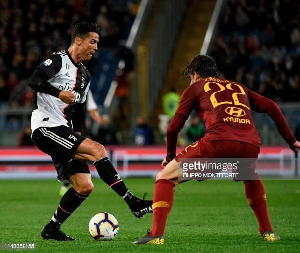Juventus' Portuguese forward Cristiano Ronaldo fights for the ball with AS Roma Italian midfielder Nicolo Zaniolo during the Italian Serie A football...