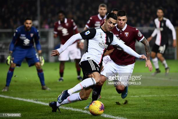 Juventus' Portuguese forward Cristiano Ronaldo fights for the ball with Torino's midfielder Daniele Baselli during the Italian Serie A football match...