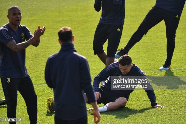 Juventus' Portuguese forward Cristiano Ronaldo gets back up after a shock as Juventus' Brazilian forward Douglas Costa reacts during a training...