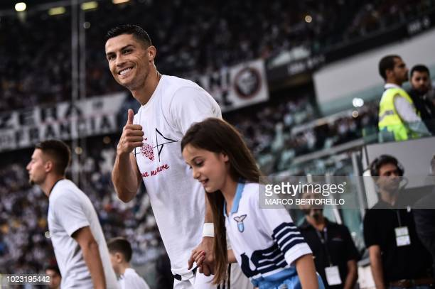 Juventus' Portuguese forward Cristiano Ronaldo gives a thumb up as he enters the pitch wearing a jersey in hommage of the victims of Genoa's Morandi...