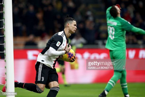 Juventus' Portuguese forward Cristiano Ronaldo grabs the ball as he celebrates after scoring a penalty past AC Milan's Italian goalkeeper Gianluigi...