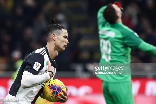 TOPSHOT Juventus' Portuguese forward Cristiano Ronaldo grabs the ball as he celebrates after scoring a penalty past AC Milan's Italian goalkeeper...