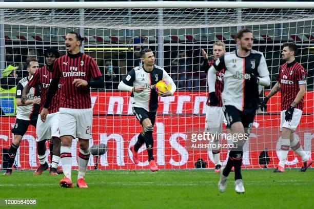 Juventus' Portuguese forward Cristiano Ronaldo grabs the ball as he celebrates after scoring a penalty as AC Milan's Swedish forward Zlatan...