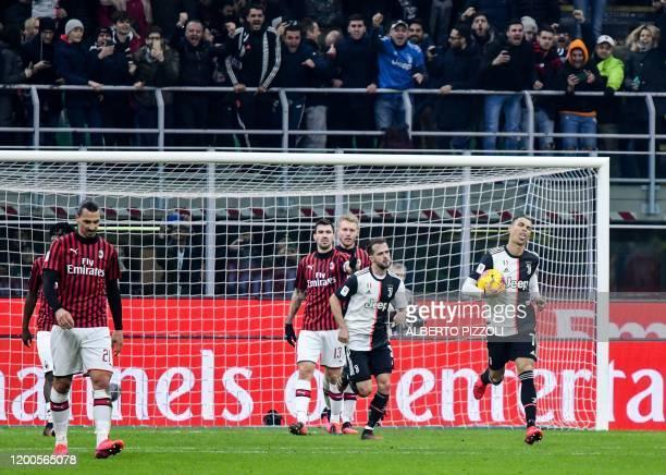Juventus' Portuguese forward Cristiano Ronaldo grabs the ball as he celebrates after scoring a penalty as AC Milan's Swedish forward Zlatan...