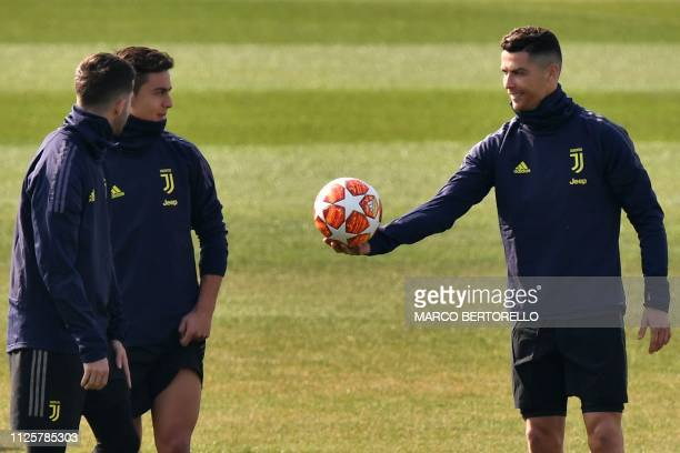 Juventus' Portuguese forward Cristiano Ronaldo hands the ball to Juventus' Argentine forward Paulo Dybala during a training session at the Continassa...