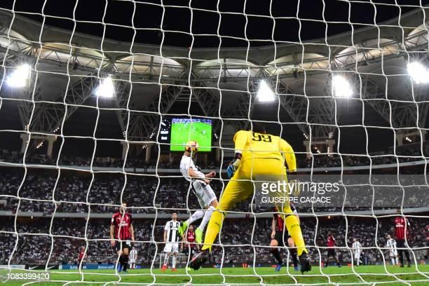 Juventus' Portuguese forward Cristiano Ronaldo heads the ball to score past AC Milan's Italian goalkeeper Gianluigi Donnarumma during their...