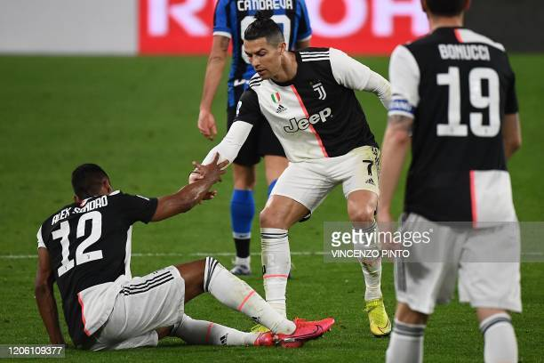 Juventus' Portuguese forward Cristiano Ronaldo helps Juventus' Brazilian defender Alex Sandro to stands up during the Italian Serie A football match...
