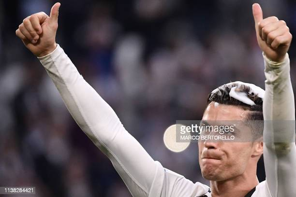 Juventus' Portuguese forward Cristiano Ronaldo his hair covered in foam acknowledges fans and celebrates after Juventus secured its 8th consecutive...