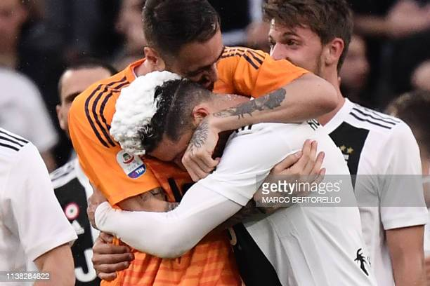 Juventus' Portuguese forward Cristiano Ronaldo his hair covered in foam and Juventus' Italian goalkeeper Carlo Pinsoglio embrace as they celebrate...