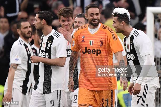 Juventus' Portuguese forward Cristiano Ronaldo his hair covered in foam and Juventus' Italian goalkeeper Carlo Pinsoglio celebrate after Juventus...