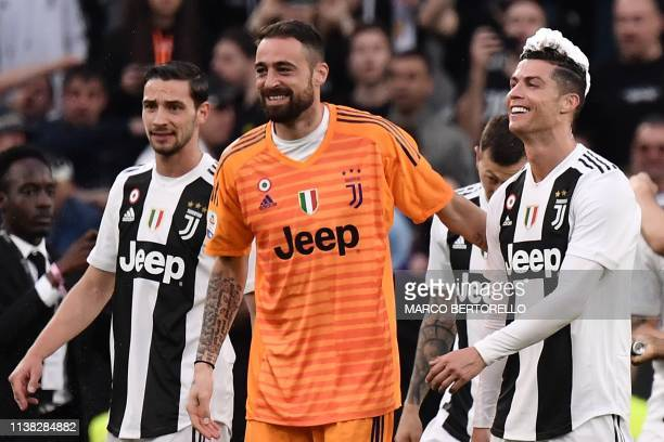 Juventus' Portuguese forward Cristiano Ronaldo his hair covered in foam celebrates with Juventus' Italian goalkeeper Carlo Pinsoglio and Juventus'...