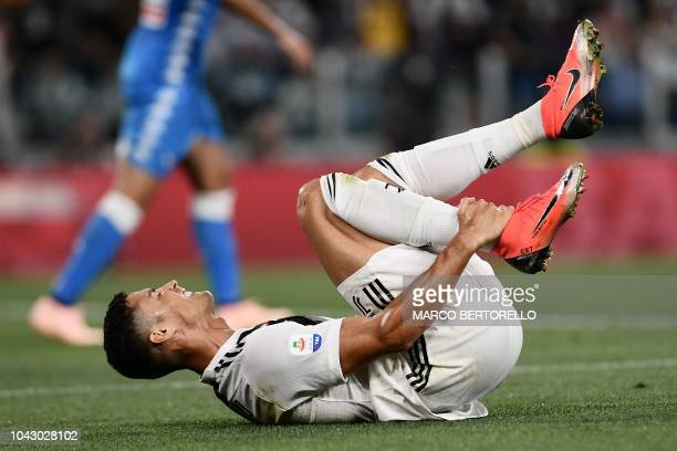 Juventus' Portuguese forward Cristiano Ronaldo holds his ankle after being fouled during the Italian Serie A football match Juventus vs Napoli on...