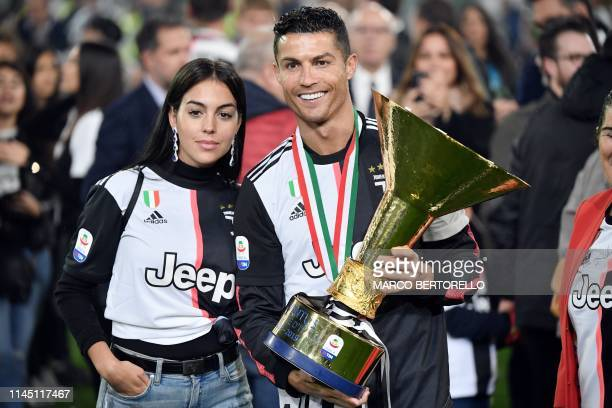 TOPSHOT Juventus' Portuguese forward Cristiano Ronaldo holds the Italian Champion's trophy next to his wife Georgina at the end of the Italian Serie...