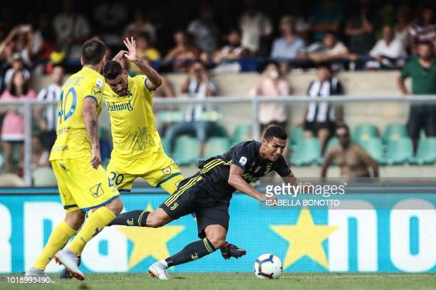 TOPSHOT Juventus' Portuguese forward Cristiano Ronaldo is tackled during the Italian Serie A football match AC Chievo vs Juventus at the...